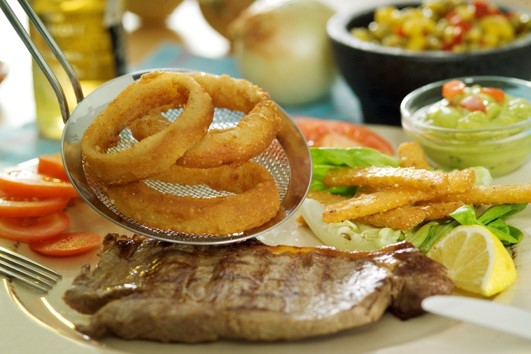 Steak with onion rings and guacamole